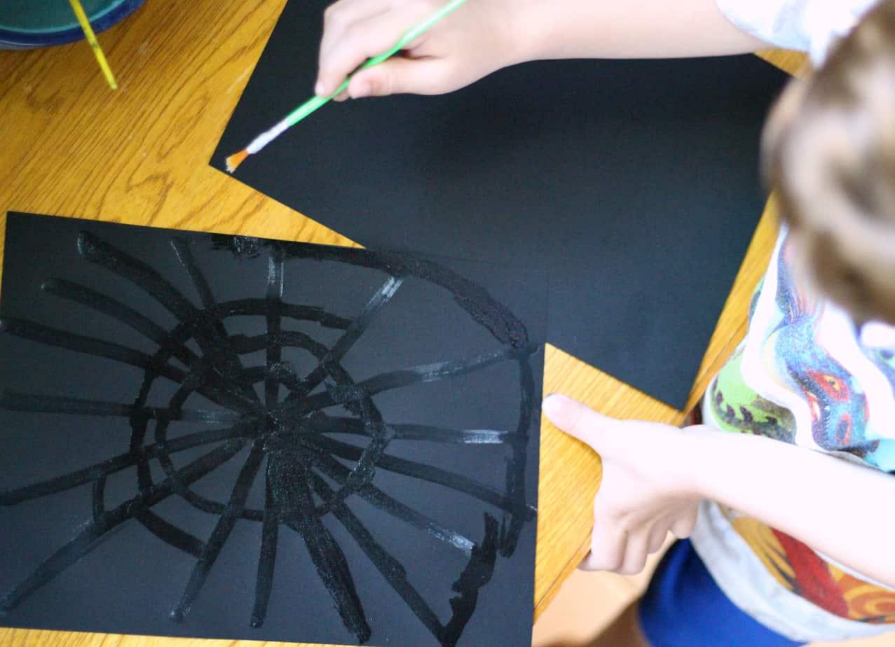 painting sparkly spiderwebs